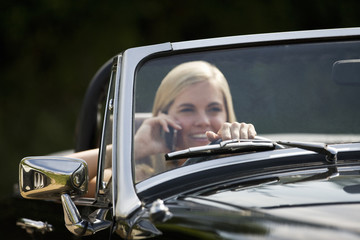 A young woman driving a black sports car holding a mobile phone