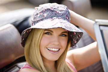 A young woman sitting in a sports car wearing a summer hat