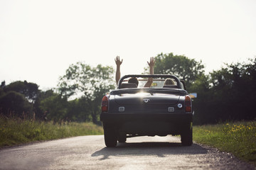 A couple driving in a sports car, man with his arms in the air