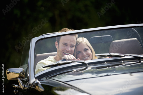 A young couple driving a black sports car