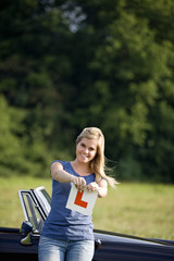 A young woman tearing up an learner driver plate