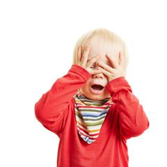 Kind spielt Verstecken und hält die Augen zu
