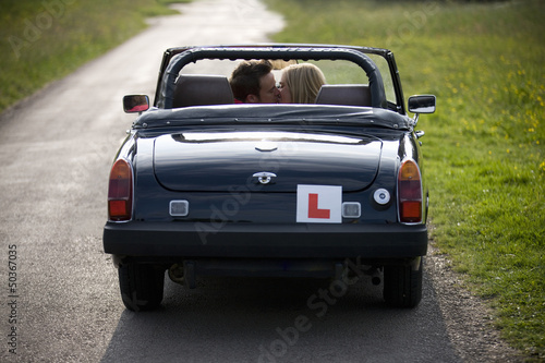 A young couple in a sports car car kissing, rear view