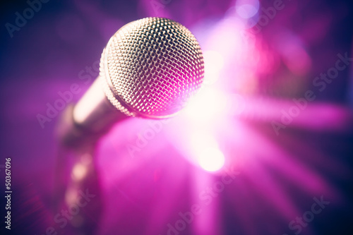 microphone on stage against purple rays background