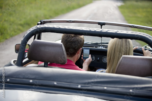 A young couple driving, man navigating using a smartphone