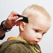 canvas print picture - Junge beim Friseur mit Kamm in den Haaren
