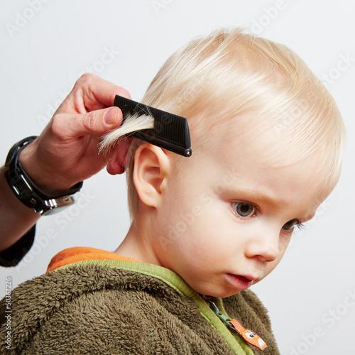 canvas print picture Junge beim Friseur mit Kamm in den Haaren