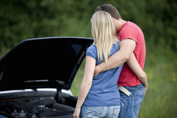 A young couple standing next to their broken down sports car