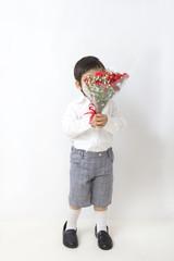 花束で顔を隠す子供