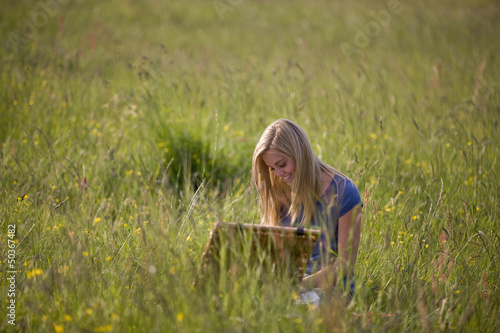 A young woman having a picnic in the countryside