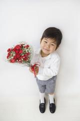 花束を持って見上げる子供