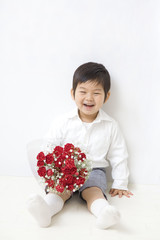 花束を持って座る子供