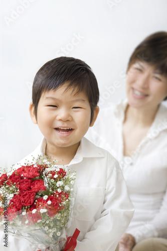 カーネーションを持つ子供と母親