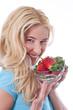 Glückliche junge Frau isoliert mit Erdbeeren in der Hand