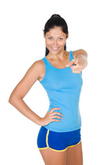 smiling athletic woman pointing his finger at you. isolated