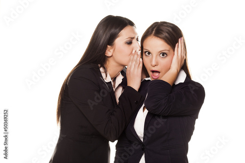 business women whispering to his colleague on her ear