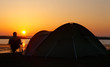 sunsets behind camper and tent