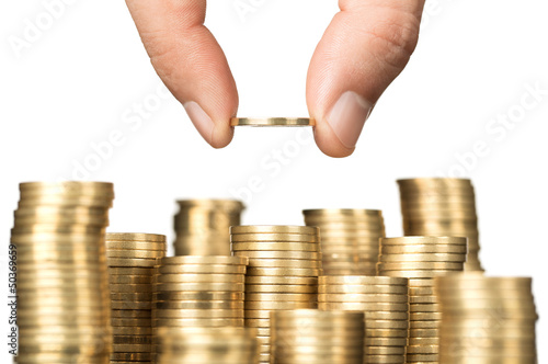 Close up of male hand stacking gold coins isolated on white