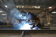 welder in factory and smoke rising