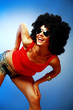 Smiling tanned woman with afro hair posing