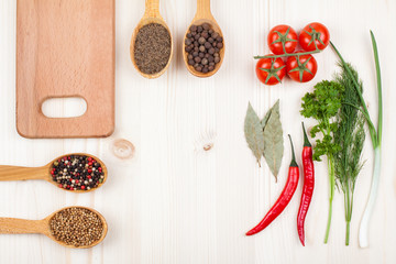 Spices, cherry tomatoes, chili, plank on wood background