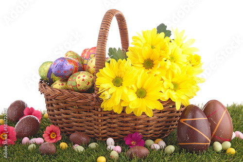 easter eggs in wicker basket with flowers