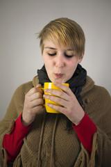 Frau trinkt heißgetränk gegen Erkältung
