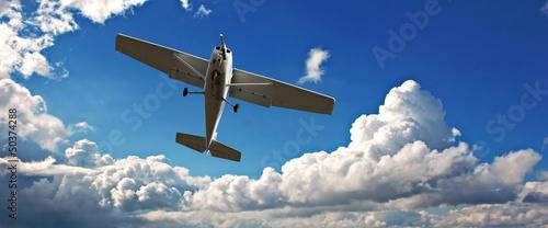Fotobehang Vliegtuig Small light aircraft on training flight