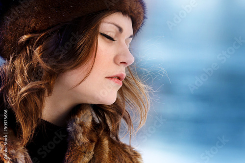 Young beaytiful women in fur hats in winter forest
