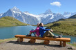 Travelers on a bench enjoying Alpine panorama