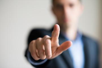 A man in a suit points finger
