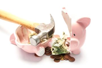 Piggy bank broken with money and hammer