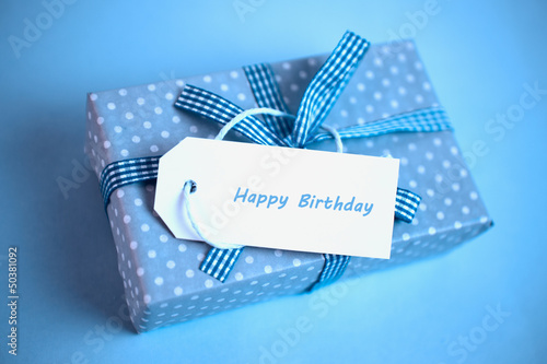 Pretty blue gift with a happy birthday card on a blue background