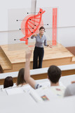 Teacher in front of futuristic interface pointing college studen
