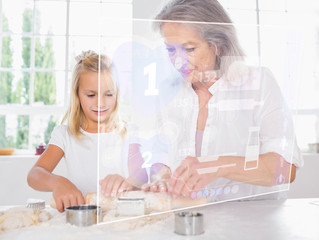 Grandmother and granddaughter baking with white interface