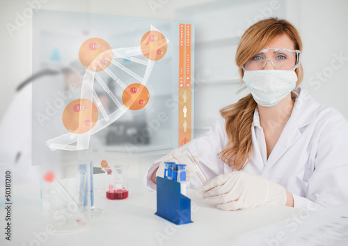Chemist working in protective suit with futuristic interface sho