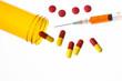 Jar of medicine spilling tablets with syringe
