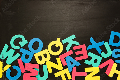 Alphabet magnets in a jumble on blackboard