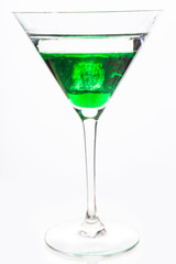 Cocktail glass with green alcohol close up