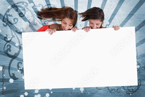 Smiling girls looking down at white copy space screen