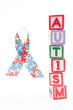 Autism awareness ribbon beside stacked blocks spelling autism