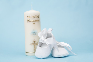 Christening candle for a boy with white baby booties
