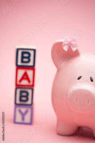 Piggy bank and blocks spelling baby