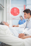 Doctor checking pulse of elderly patient beside screen displayin