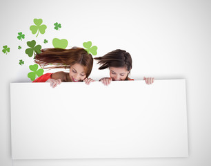 Girls looking down at blank placard with shamrock background