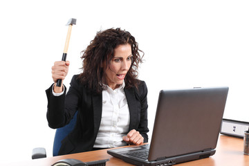 Mature businesswoman trying to destroy a laptop with a hammer