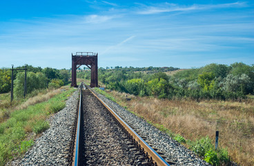 Ukrainian summer landscape with small railroad bridge.
