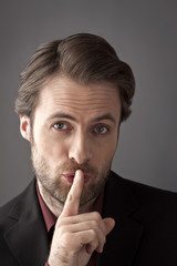 Businessman with finger on his lips trying to hide a secret