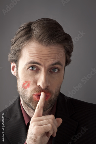 Man with woman lipstick kiss on his cheek - secret love affair