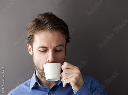 Sleepy office worker man drinking morning coffee
